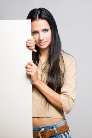 sexy sweater: Portrait of a beautiful brunette woman holding a blank white sheet.