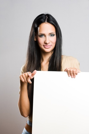 Portrait of a beautiful brunette woman holding a blank white sheet. photo