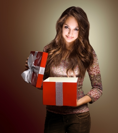 Portrait of a beautiful young brunette peeking inside shiny red gift box in creative lighting. photo