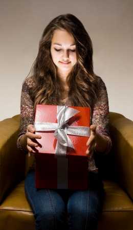 Portrait of a beautiful young brunette peeking inside shiny red gift box in creative lighting. Stock Photo - 15785436