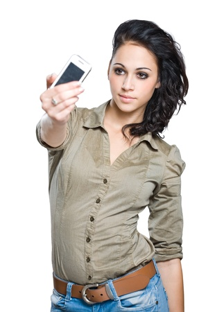 Portrait of a beautiful young brunette taking a picture of herself with a cell phone  photo