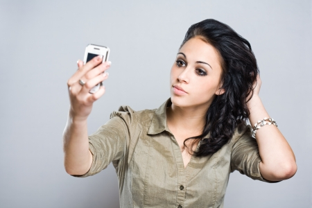 sexy pictures: A gorgeous brunette woman taking a picture of herself with a cell phone