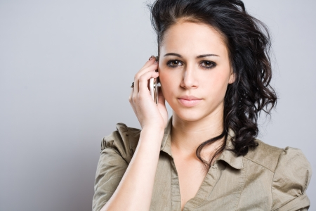 Portrait of a young brunette using her mobile phone with worried facial expression  photo