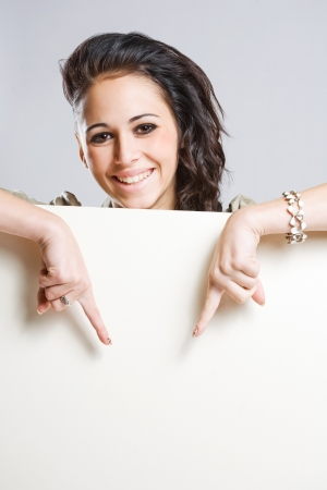 Portrait of an attractive young brunette woman holding blank billboard. photo