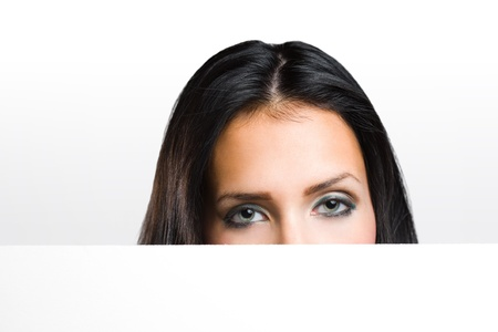 Portrait of a beautiful brunette peeking out from behind blank white banner. photo