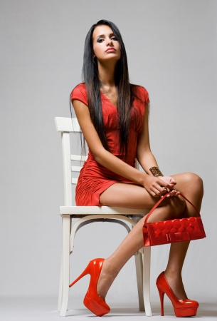 Gorgeous sensual young brunette model in red hot outfit. photo