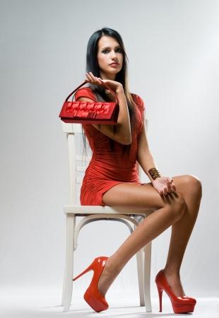 beautiful legs: Moody shot of stylish brunette fashion beauty on white chair.  Stock Photo