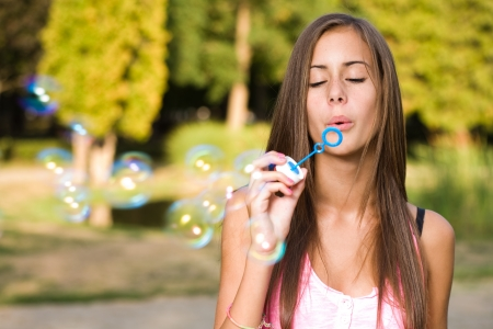 Dreamy blond teen beauty blowing soap bubbles. photo