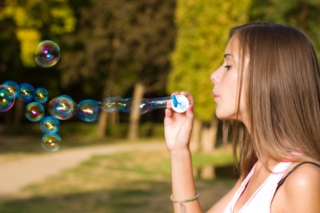 Gorgeous young teen girl blowing bubbles. photo