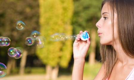 woman blowing: Dreamy blond teen beauty blowing soap bubbles.