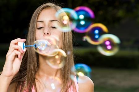 girl blowing: Dreamy blond teen beauty blowing soap bubbles.