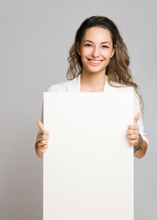 Portrait of a cheerful young brunette woman holding a white blank banner Stock Photo - 16128380