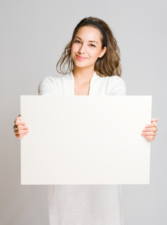 ad sign: Portrait of a cheerful young brunette woman holding a white blank banner  Stock Photo