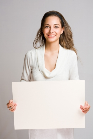 people holding sign: Happy beautiful young woman with empty billboard