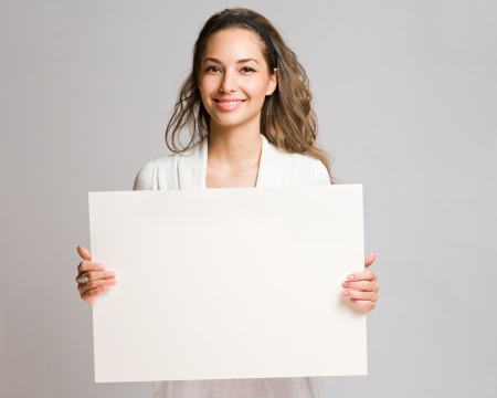 Portrait of a cheerful young brunette woman holding a white blank banner