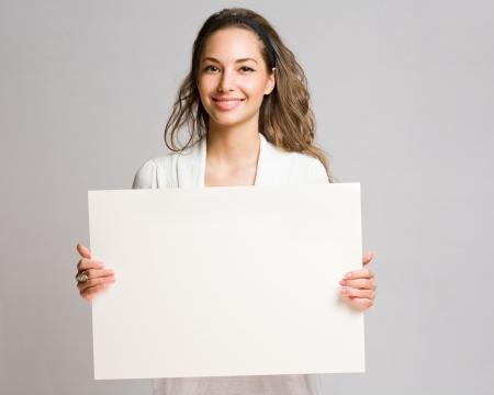 terra arrendada: Retrato de um alegre jovem morena mulher segurando uma bandeira em branco