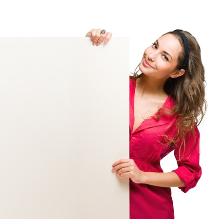 Portrait of a cheerful young brunette woman holding a white blank banner  photo