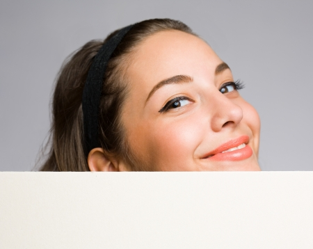 Happy beautiful young woman with empty billboard  photo