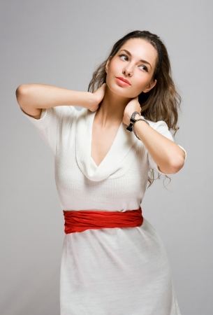 Fashionable young brunette beauty posing in white dress sweater and red belt  photo