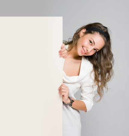 Gorgeous young brunette woman holding blank white billboard  photo