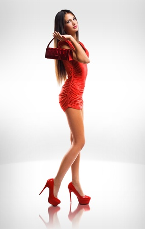 Portrait of slender  long legged brunette beauty in little red dress. photo