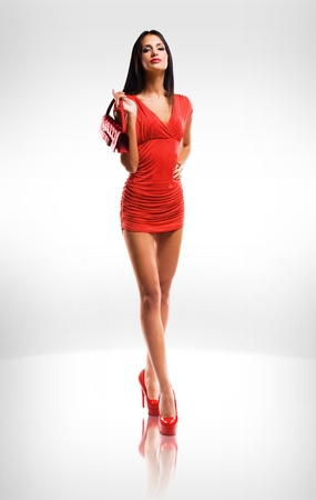 colorful dress: Portrait of very fashionable slender brunette beauty in red hot little dress.