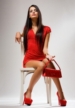 handbag model: Very fashionable young brunette beauty posing on white chair. Stock Photo