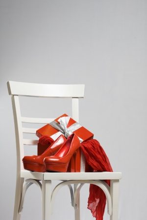 Bright red feminine gifts next to open box. photo