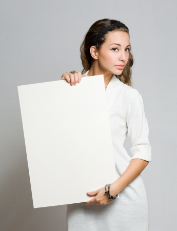 Freindly young brunette beauty holding white blank banner  photo