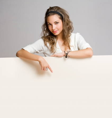 Portrait of a beautiful young brunette woman with blank billboard sheet  Stock Photo