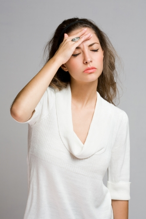 forgetful: Portrait of stressed looking brunette beauty in white sweater.