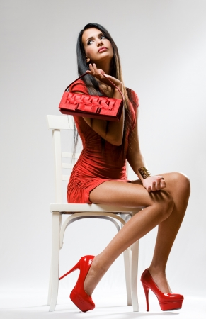 women posing: Portrait of a sensual fashion model in full red outfit.
