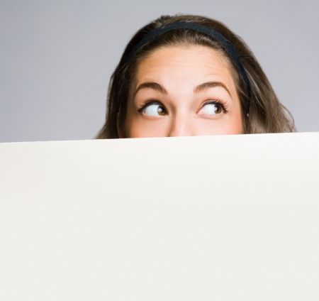 shy woman: Cute funny young brunette smiling behind large white blank billboard.