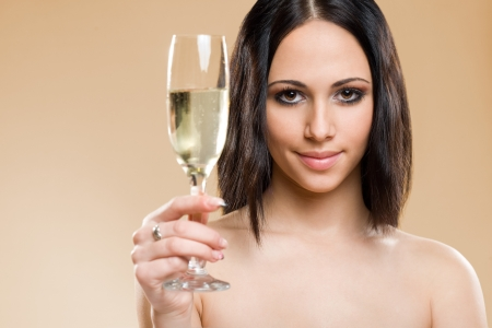 Portrait of gorgeous young brunette with glass of champagne on golden background. photo