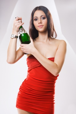 Half length portrait of a sensual woman in red dress with bottle of champagne. photo