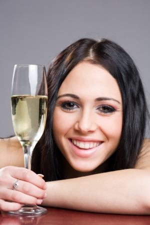 Portrait of cheerful young brunette woman with glass of sparkling champagne. photo