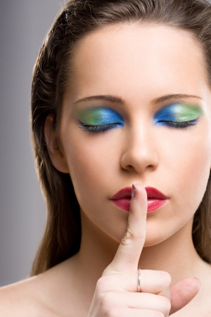 Portrait of a brunette beauty in creative colorful makeup making silence gesture. Stock Photo - 16695382