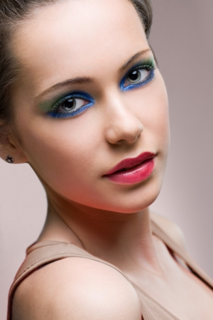 Intense beauty portrait of a gorgeous brunette in colorful makeup. photo