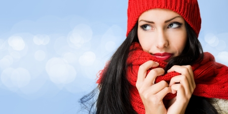 Brunette beauty in winter fashion on blue background with white glow circle pattern  photo