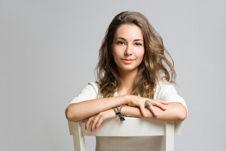 Studio portrait of friendly pensive young brunette beauty
