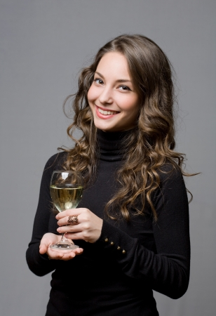 Festive young brunette beauty holding glass of wine. photo