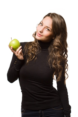 Fit slender young brunette woman holding apple with a smile. photo