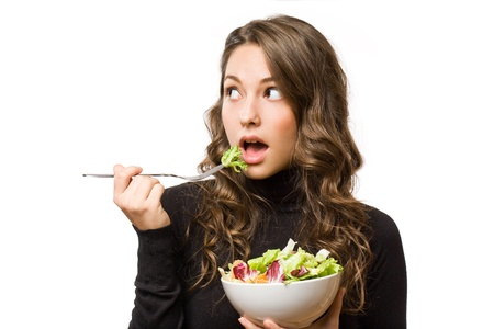 Expressive young brunette beauty with bowl of fresh salad. photo