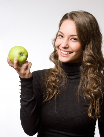 Cute healthy smiling young brunette holding fresh green apple. photo