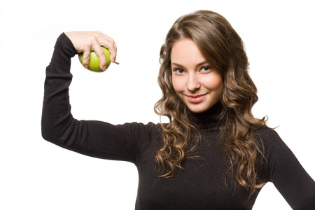 Portrait of a fit young brunette holding juicy fresh green apple. photo