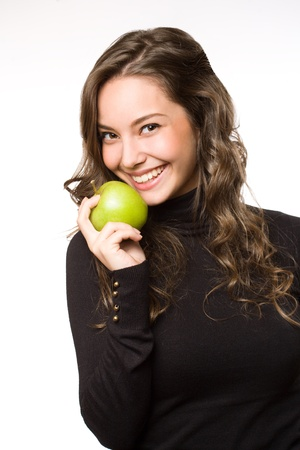 Gorgeous young brunette woman showing off fresh green apple. photo