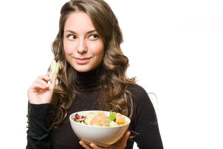 Portrait of an attractive brunette woman with a bowl of salad. photo