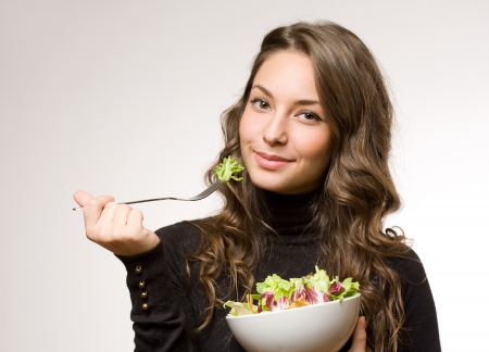 Portrait of a cheerful young brunette woman having salad. photo