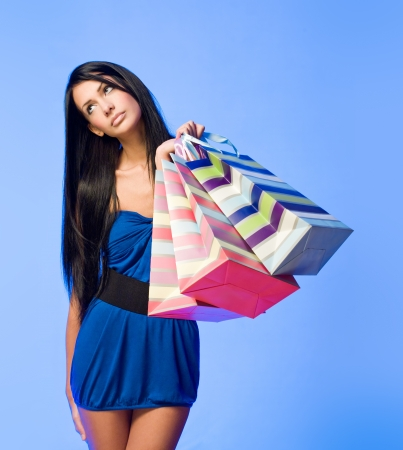 Colorful portrait of a gorgeous young brunette woman with shopping bags. photo