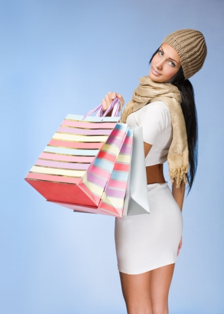 Colorful portrait of a gorgeous young brunette woman with shopping bags. Stock Photo - 17424771